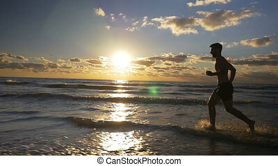 Runner doing workout on a beautiful beach at sunrise in slow...