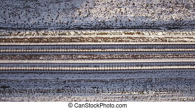 AERIAL. Camera flight above train tracks covered by snow. Overhead footage. 4k
