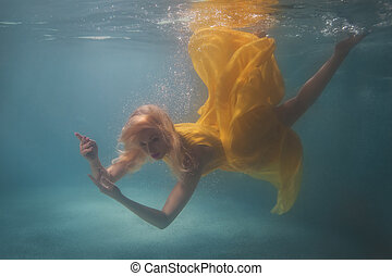 Woman in yellow dress under water. - Woman in yellow dress...