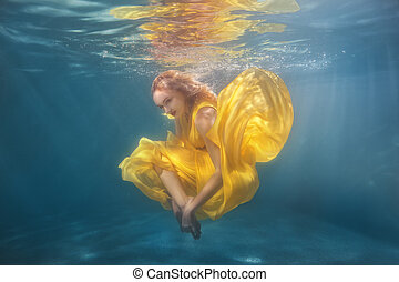 Woman dancing underwater. - Woman in yellow dress dancing...