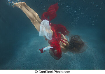 Woman in red dress underwater. - A woman in a red dress...