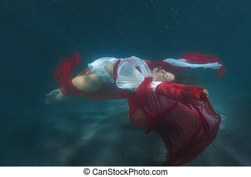 Woman in red dress dancing underwater. - Woman in red dress...