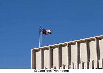 American flag flying proudly above a building.