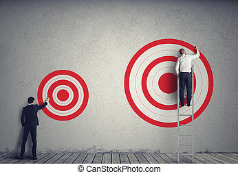Hitting bigger business target - Businessman drawing a...