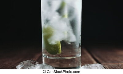 Glass is poured with water - Glass with ice filled with...