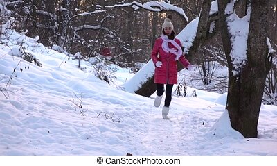 Slow motion shot of beautiful happy girl in red jacket running towards the camera in snowy winter forest