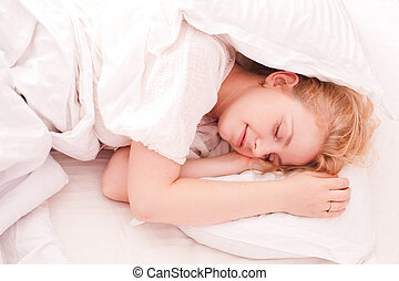 Woman sleeping in white bed