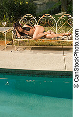 Young sexy woman in swimsuit sunbathing by pool