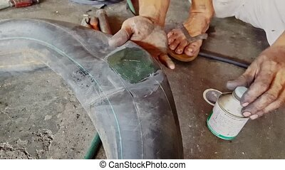 Closeup Man Hands Put Glue on Wheel Inner Tube - closeup...