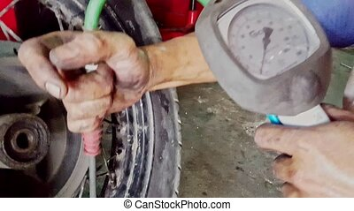 Closeup Man Controls Pressure in Tire with Manometer in Shop...