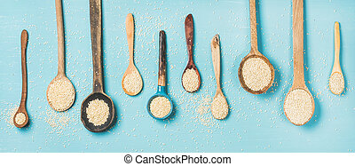 Quinoa seeds in different spoons over blue background, top...