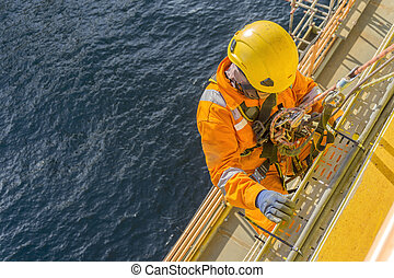 Oil and gas - Man working overboard. Abseiler complete with...