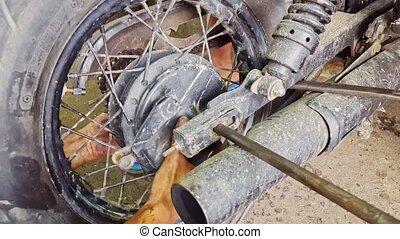 Closeup Man Fits Axle in Motorcycle Wheel in Repair-shop -...