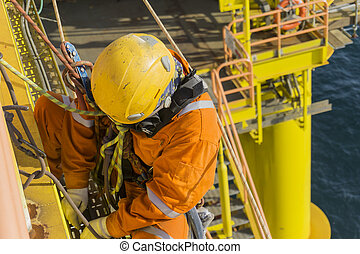 Oil and gas - Man working overboard. Abseiler hanging on...