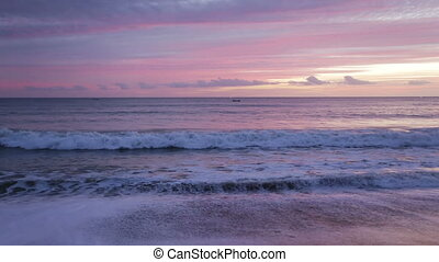 Waves in magically pink sunset over the sea.