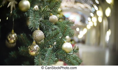 Slider view of golden mirror and matte balls. New Year's and abstract blurred shopping mall background with Christmas tree decorations.