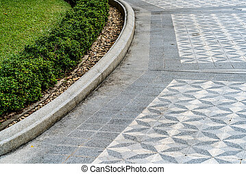 Concrete block pathway with curve of trimmed bush plants in...