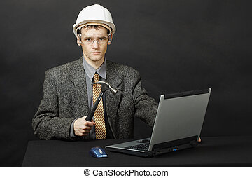 Man in helmet with hammer repairs computer