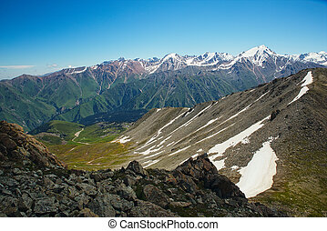 Green grassy mountain valley with ice peaks, Central...