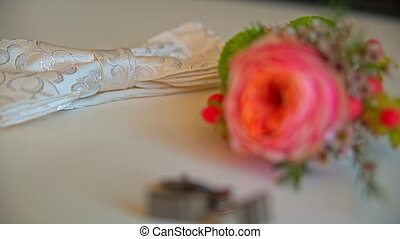 on the table lay a beautiful boutonniere and cufflinks.