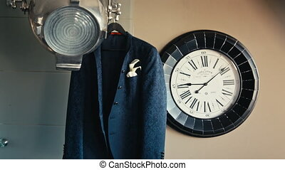 men's jacket hanging on the floodlight near the clock.