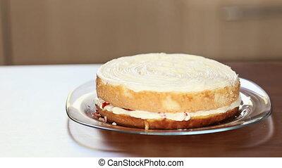 chef squeezes jam on cake