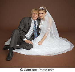 Happy newly-married couple on brown background - Happy...