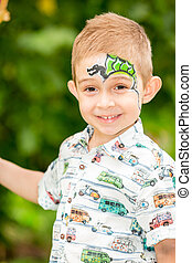 Cute little child boy with aqua make-up in park on nature at...