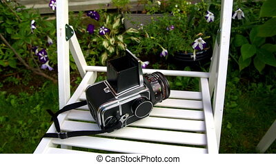 camera Hasselblad is on a white chair on the lawn