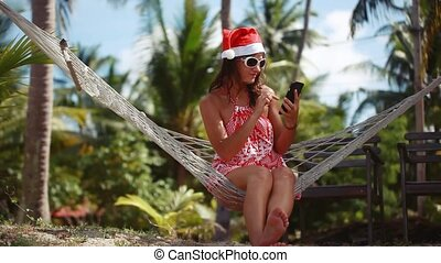 Young beautiful woman in sunglasses and christmas hat in hammock uses mobile phone on tropical beach celebrating Christmas on Koh Samui. Thailand. 1920x1080
