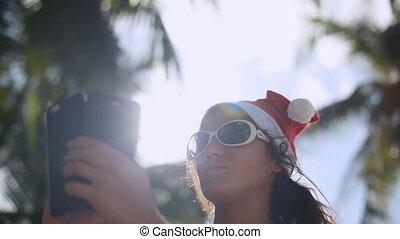 Beautiful woman in santa claus hat making selfie through the sun on Koh Samui beach. Thailand. Christmas modern technology travel concept. 1920x1080