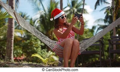Young beautiful woman in sunglasses and christmas hat in...