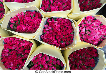 A bouquet of roses wrapped with paper for sale at Pak Khlong...