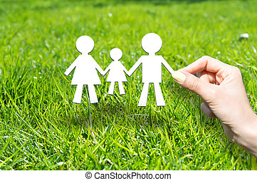 Family insurance concept with family made out of cardboard on green grass