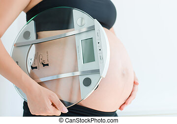 weight gain during pregnancy with pregnant woman holding...
