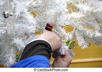Hanging Christmas adornments on the Christmas tree
