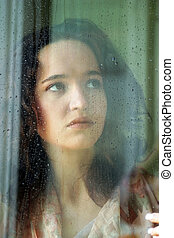 The girl behind glass - Woman with sad smile behind a wet...
