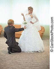 Groom with bride funny pose in hall - The groom with the...
