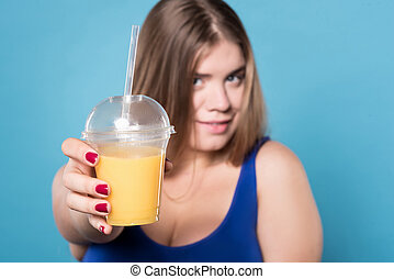 Young chubby lady holding juice - Try it. Close up of glass...