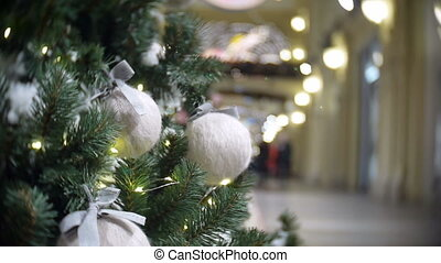 Slider view of white wool balls and lights. New Year's and abstract blurred shopping mall background with Christmas tree decorations.