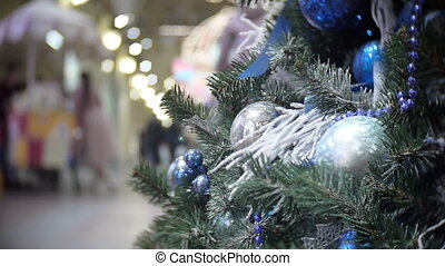 Slider view of blue mirror and matte balls and snow. New Year's and abstract blurred shopping mall background with Christmas tree decorations.
