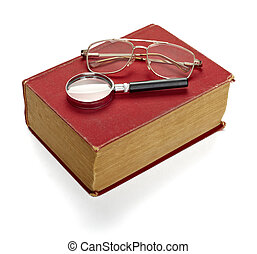 close up of an old book, loupe and eyeglasses on white background with clipping path