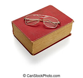 close up of an old book and eyeglasses on white background with clipping path