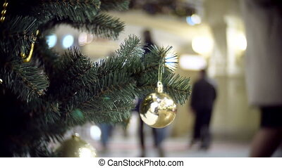 Slider view of small golden mirror ball. New Year's and abstract blurred shopping mall background with Christmas tree decorations.