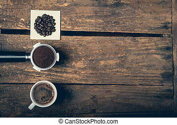 Coffee beans, ground and cup of espresso on the wooden...