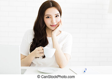 happy young woman with coffee in living room