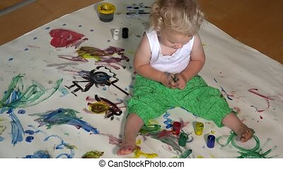 Toddler boy put dirty fingers in colorful paint. Child have...