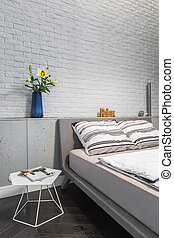 Bedroom with matrimonial bed and white brick wall
