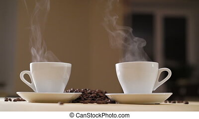 Two white cups of delicious coffee on the table with roasted...