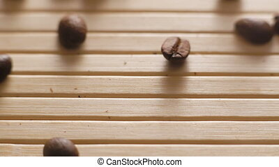 Roasted coffee beans falling on the on the table surface in...